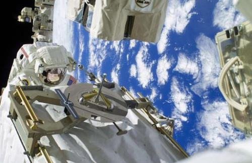This December 22, 2013 NASA image shows astronaut Rick Mastracchio (L) participating in the first Expedition 38 spacewalk design