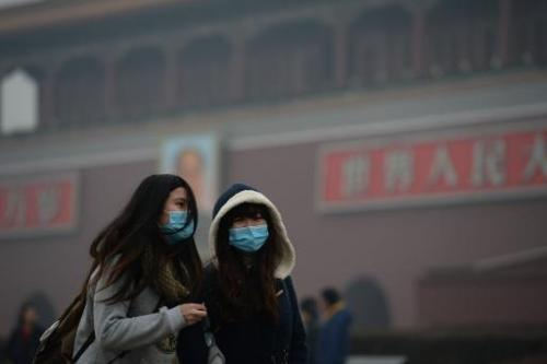 Two girls walk through a haze-shrouded Tiananmen Square in Beijing on February 23, 2014