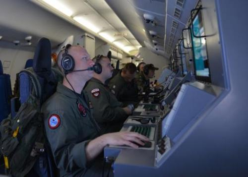 US Navy crew members assist in search and rescue operations for Malaysia Airlines flight MH370, March 16, 2014