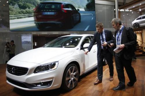 Visitors check out a Volvo car on display during the 'Auto China 2014' Beijing International Automotive Exhibition, on April 20,