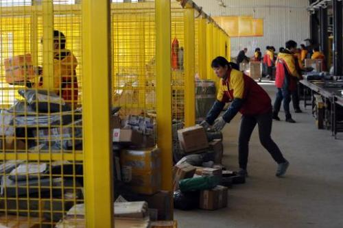 Workers sort out packages at an express delivery company in Beijing on November 12, 2013