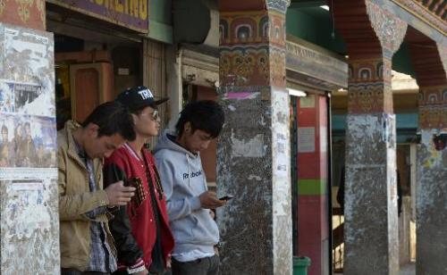 Young Bhutanese residents use mobile phones to surf the Internet as they stand on a street in Thimphu, February 20, 2014