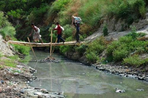 Youths cross a bamboo bridge over a polluted tributary that runs into the river Ganges in Kanpur on June 26, 2014