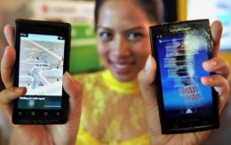 A model displays smartphones with Google's mobile operating system Android