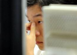 A South Korean dealer checks a computer screen inside the dealing hall at the Korean Exchange Bank in Seoul