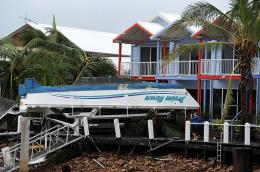 A catamaran lies upsidedown on the porch of a luxury waterfront home