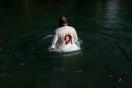 A Christian pilgrim walks in the waters of the Jordan River in 2009