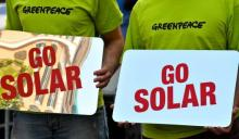 Activists of the environmental group Greenpeace hold banners reading,