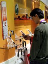 A man test mobiles at the Sony Ericsson stand at the 3GSM World Congress