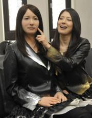 "A model (R) touches the face of a humanoid robot called ""Geminoid-F"" (L)"
