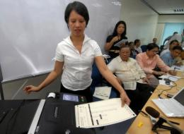 An employee (L) of Smartmatic demonstrates how an electoral automation machine works in Manila