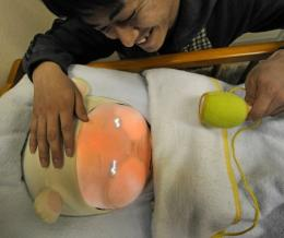 An engineering student soothes Yotaro, a robot which emulates a real baby at Tsukuba University in Japan