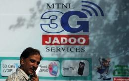 An Indian man walks past an advertisement for 3G telecom services in New Delhi in April