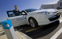An Israeli man stops an electric car next to a charging station at the first electric vehicle demonstration centre