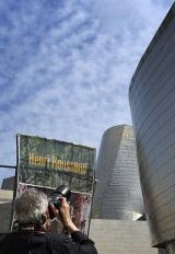 A photographer takes a picture of the poster announcing a Guggenheim Bilbao museum temporary exhibition