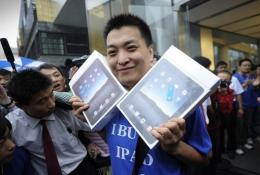 Apple customer Han Ziwen holds up his ipads
