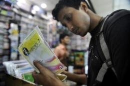 A shopper looks at counterfeit computer programmes in Dhaka, Banglasdesh