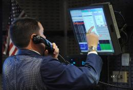 A stock specialist works at a trading post on the floor of the New York Stock Exchange