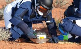 A team of scientists inspect the capsule carried by the Japanese Hayabusa spacecraft after it parachuted into Australia
