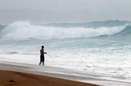 A tourist takes a dip into the sea in Cabo San Lucas, Baja California, Mexico as a hurricane approaches in 2006