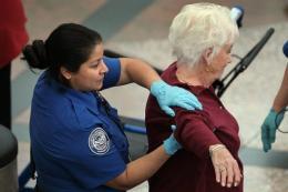 A traveler undergoes an enhanced pat down by a TSA agent