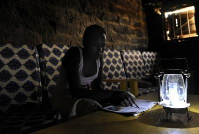 A villager at Chumbi village, some 50 km southeast of Nairobi, reads with the aid of a solar-powered lamp