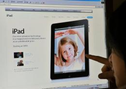 A woman looks towards a website showing the latest Apple iPad