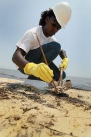 A worker cleans oily globs that washed ashore in Waveland, Mississippi