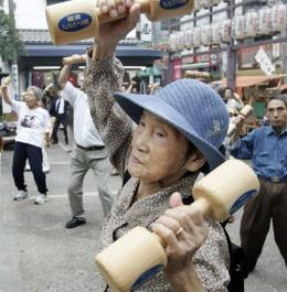 Elderly people work out with wooden dumb-bells at a temple in Tokyo
