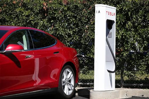Tesla model s sedan is plugged into a supercharger outside the