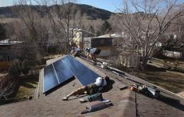 Installers for Namaste Solar connect solar panels to the roof of a home