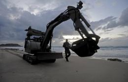 Israeli police explosives experts use a bomb disposal robot to scan the beach
