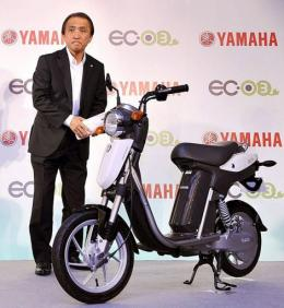 Japan's Yamaha Motor President Hiroyuki Yanagi stands next to the company's new electric commuter vehicle EC-03
