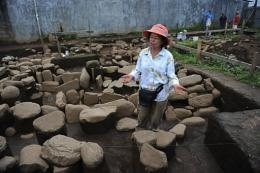 Maritza Gutierrez works on tombs made with stones at an indigenous cemetery
