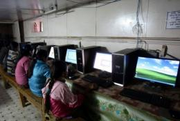 Nepalese girls surf the Internet in the village of Nagi, some 200 kms west of Kathmand