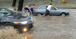 Passerbys help push a car down a flooded road in central Melbourne