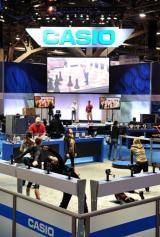 Performers stretch at the Casio display before the opening of the 2010 International Consumer Electronics Show