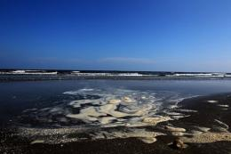 Pools of dispersed oil collect on a section of the public beach on August 10 in Grand Isle, Louisiana
