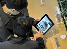 South Korean men look at Apple's iPad at a KT shop during its launch in Seoul