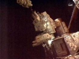 Spacewalking astronauts plug in new cooling pump (AP)
