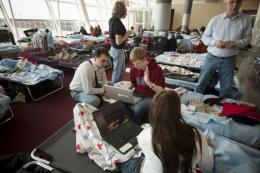 Stranded travelers use laptop computers while sitting on cots at JFK's Terminal 4