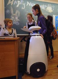 Students speak with their teacher near Stepan the robot
