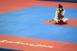 Taiwan's taekwondo hopeful Yang Shu-chun sits on the mat, refusing to leave in protest