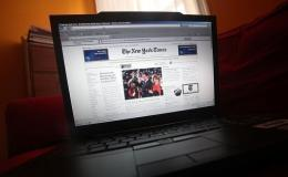The NYTimes.com website is displayed on a laptop