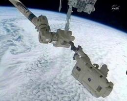 This NASA TV framegrab shows Discovery shuttle astronaut Steve Bowen (R) on the end of the robotic arm