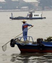 Workers clear waste from the heavily polluted Pearl River in southern China's Guangdong province