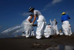 Workers contracted by BP clean oil from the beach at the Grand Isle East State Park