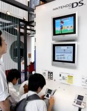 Young boys play Japanese video game giant Nintendo's portable video game console